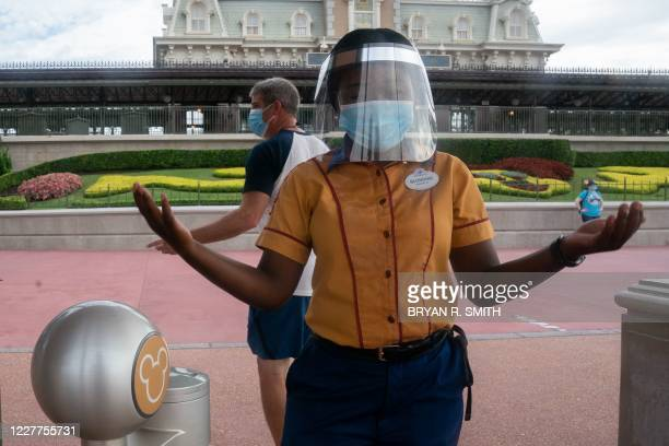 An employee at Walt Disney World Resort's Magic Kingdom wears a facemask and face shield at the entrance to the park during the COVID-19 pandemic in...