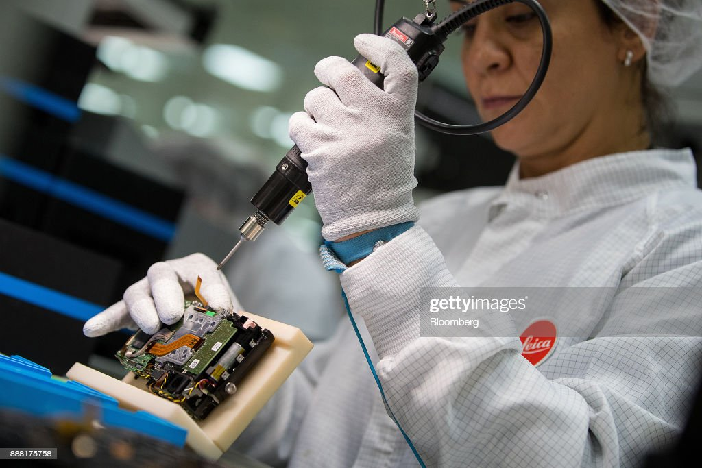 An employee attaches a 24-megapixel sensor to a Leica M10 range-finder digital camera during assembly at the Leica Camera AG factory in Wetzlar, Germany, on Tuesday, Nov. 28, 2017. German factory orders unexpectedly rose for a third month in October, in a sign that Europes largest economy will carry its strong momentum into 2018. Photographer: Krisztian Bocsi/Bloomberg via Getty Images