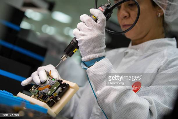 An employee attaches a 24megapixel sensor to a Leica M10 rangefinder digital camera during assembly at the Leica Camera AG factory in Wetzlar Germany...