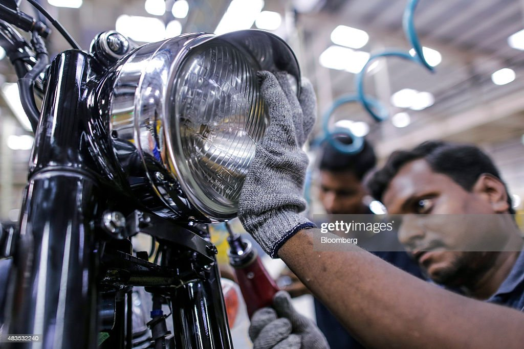 An employee attaches a headlight to a Royal Enfield Motors Ltd Classic 350 motorcycle moving on a conveyor on the production line at the company`s...