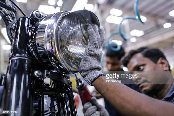 An employee attaches a headlight to a Royal Enfield Motors Ltd Classic 350 motorcycle moving on a conveyor on the production line at the company's...