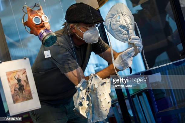 An employee attaches a mask as an exhibit in the new Documentation Center for Displacement, Expulsion and Reconciliation on June 16, 2021 in Berlin,...