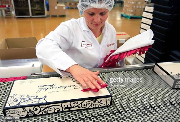 An employee attaches a ribbon to a Continental chocolate box at the Thorntons Plc chocolate factory in Alfreton UK on Thursday Aug 2 2012 The cost of...