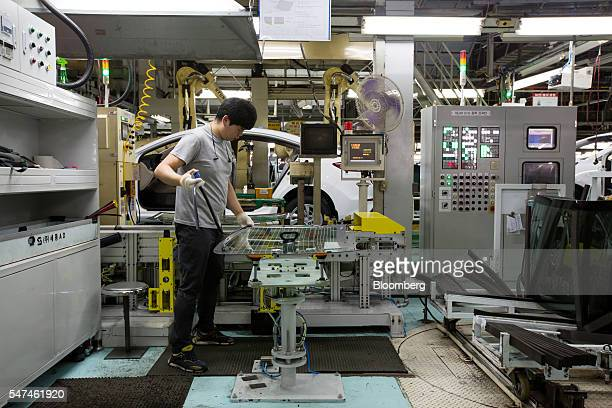 An employee attaches a rubber seal to a windscreen for a Hyundai Motor Co. Elantra vehicle on the production line at the company's plant in Ulsan,...
