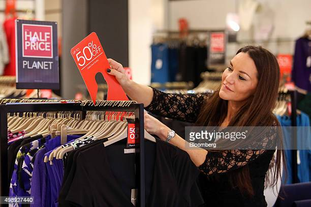 An employee attaches an up to 50 percent discount sign to a clothes rail inside a Debenhams Plc department store on Black Friday in London UK on...