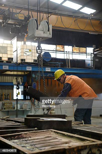 An employee attaches the hook of an overhead crane to a metal mold in the foundry at the Backwell IXL plant in Geelong Australia on Tuesday May 20...