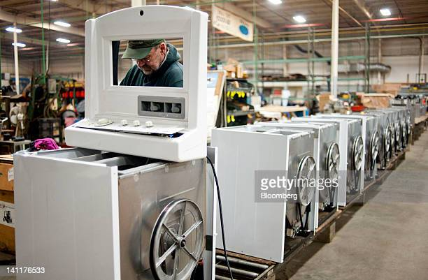 An employee attaches the top to a dryer on the assembly line at Staber Industries Inc in Groveport Ohio US on Thursday March 8 2012The US Census...