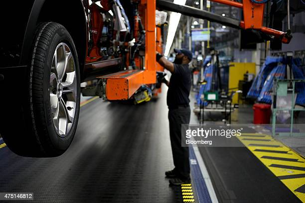 An employee attaches wheels to a Bayerische Motoren Werke AG vehicle on the assembly line at the BMW Manufacturing Co assembly plant in Greer South...