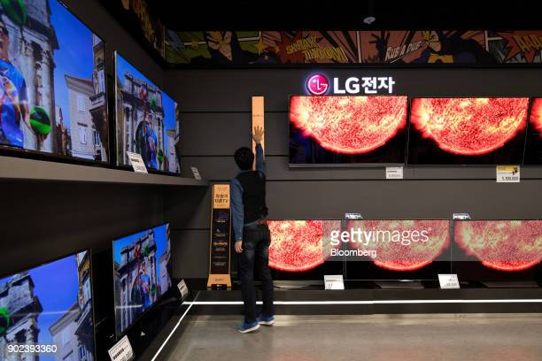 An employee attends to a sign next to LG Electronics Inc curved organic lightemitting diode televisions at an EMart Inc Electro Mart store in Gimpo...