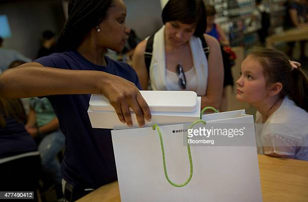 An employee bags an Apple Watch for a customer at an Apple Inc store in New York US on Wednesday June 17 2015 Apple Inc is rolling out a 'Reserve...