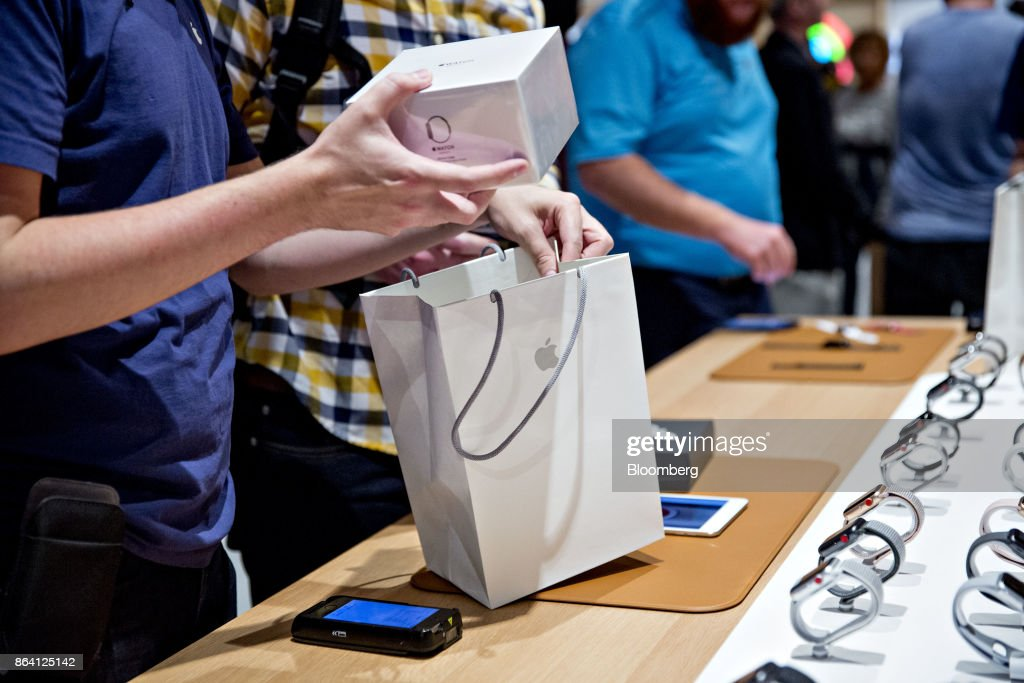 An employee bags an Apple Watch for a customer during the opening of the new Apple Inc. Michigan Avenue store in Chicago, Illinois, U.S., on Friday, Oct. 20, 2017. The building features exterior walls made entirely of glass with four interior columns supporting a 111-by-98 foot carbon-fiber roof, designed to minimize the boundary between the city and the Chicago River. Photographer: Daniel Acker/Bloomberg via Getty Images