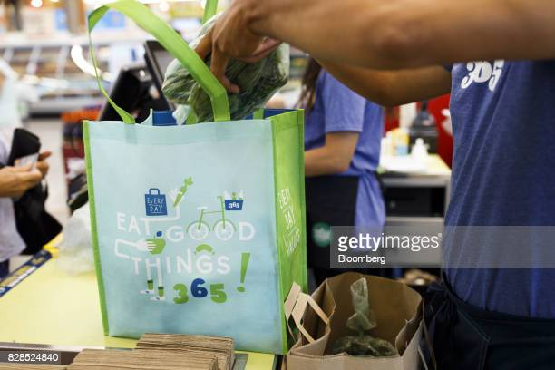 An employee bags groceries for a customer during the grand opening of a Whole Foods Market 365 location in Santa Monica California US on Wednesday...