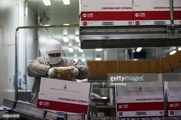 An employee boxes bags of crumbed chicken pieces in the packaging section at the Charoen Pokphand Foods Pcl processing plant in Chok Chai Nakhon...