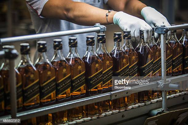 An employee boxes bottles of Johnnie Walker Black Label Scotch on the postponement line at the Diageo Plc International Supply Center and Technical...