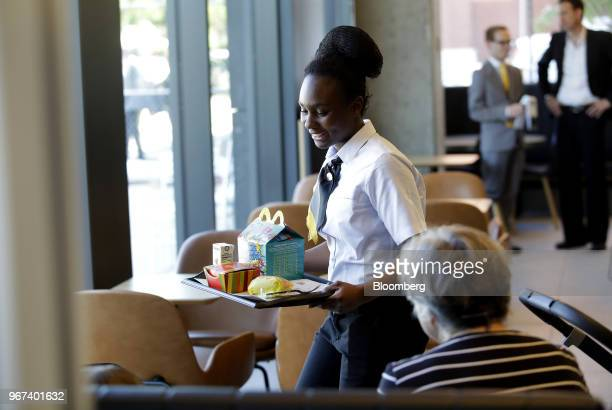 An employee brings an order to customers at the restaurant inside the new McDonald's Corp. Headquarters in Chicago, Illinois, U.S., on Monday, June...