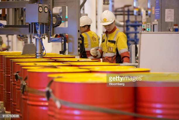 An employee caps oil drums containing lubricant oil at the Royal Dutch Shell Plc lubricants blending plant in Torzhok Russia on Wednesday Feb 7 2018...