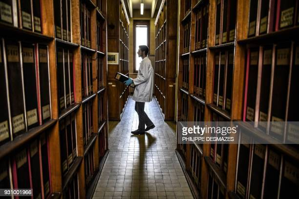 An employee carries a binder containing herbarium paper sheets to have the sheets digitalizated on March 12 2018 at the Claude Bernard LyonI...