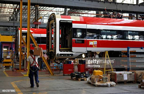 An employee carries a box past a rail carriage on the Frecciarossa 1000 highspeed train production line at AnsaldoBreda SpA's railcar plant in...
