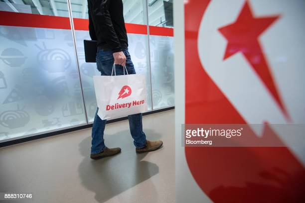 An employee carries a branded paper bag inside the Delivery Hero AG headquarter offices in Berlin Germany on Friday Dec 8 2017 Delivery Hero competes...