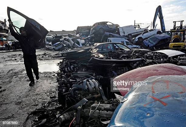 An employee carries a car door at Allo Casse Auto's car demolition site in Athis Mons France on Wednesday Feb 24 2010 French consumer spending...