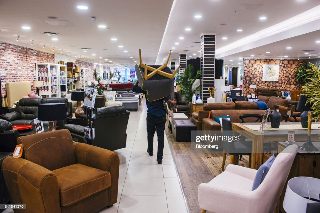 An Employee Carries A Chair Past Displays Of Home Furnishings Inside A Rochester  Furniture Store Operated