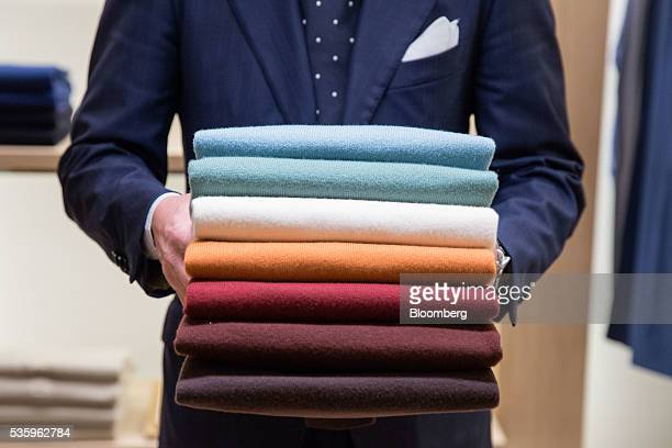 An employee carries a display of cashmere pullovers in a Loro Piana SpA store in Milan Italy on Tuesday May 10 2016 About threequarters of Loro...