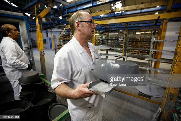 An employee carries a freshly painted cast iron AGA casserole dish produced by Aga Rangemaster Plc during the manufacturing process at the company's...