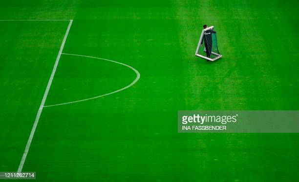 An employee carries a goal during a training session at the club's training grounds in Gelsenkirchen, western Germany on April 29, 2020 amid the new...
