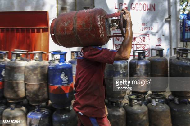 An employee carries a Hindustan Petroleum Corp liquefied petroleum gas cylinder on his shoulder at a depot operated by the company in Mumbai India on...