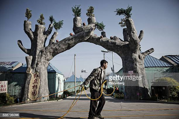 """An employee carries a hose past the entrance to the """"Red Beans Mansion"""" resort and theme park, on the site of a former coal mine, near Gujiao, Shanxi..."""