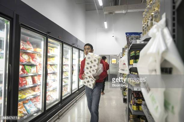 An employee carries a packet of toilet paper while fulfilling an electronic order in a WalMart Stores Inc miniwarehouse for the company's onehour...