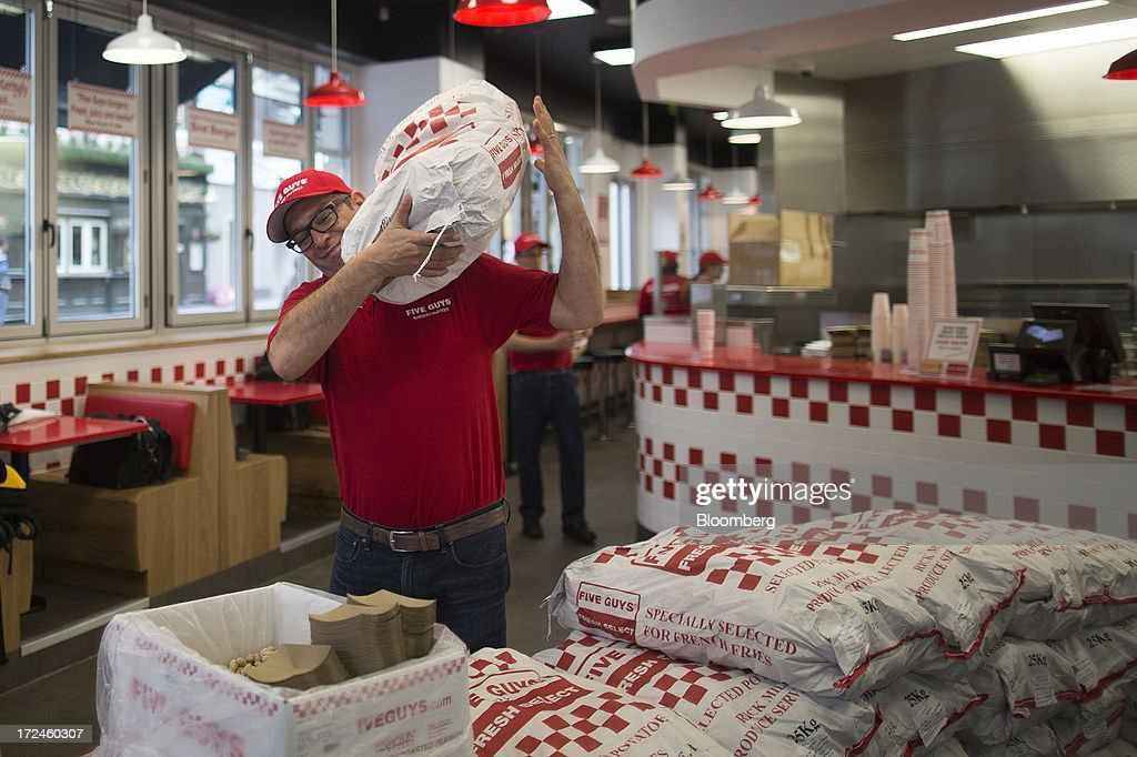 An employee carries a sack of Dutch potatoes as he walks through the first U.K. outlet of U.S. burger restaurant chain Five Guys in London, U.K., on Tuesday, July 2, 2013. Five Guys, which is set to open its first U.K. store in Covent Garden on July 4, is a family outfit that started in Washington, D.C., in 1986, and has expanded to more than 1,000 locations in the U.S. and Canada. Photographer: Simon Dawson/Bloomberg via Getty Images