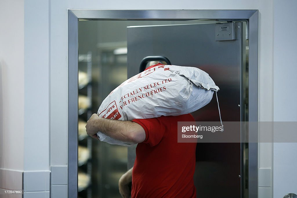 An employee carries a sack of Dutch potatoes into the kitchen at U.S. burger restaurant chain Five Guys in London, U.K., on Tuesday, July 2, 2013. Five Guys, which is set to open its first U.K. store in Covent Garden on July 4, is a family outfit that started in Washington, D.C., in 1986, and has expanded to more than 1,000 locations in the U.S. and Canada. Photographer: Simon Dawson/Bloomberg via Getty Images