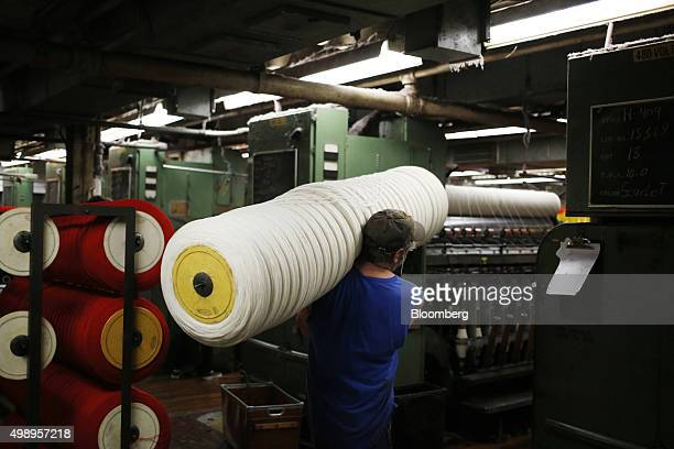 An employee carries a spool of white wool yarn at the Woolrich Inc woolen mill in Woolrich Pennsylvania US on Wednesday Nov 4 2015 Woolrich the...