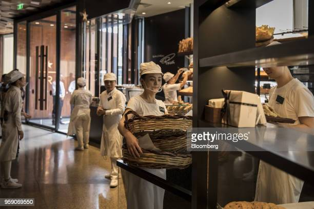 An employee carries a stack of baskets at the Princi bakery inside the Starbucks Corp Reserve Roastery store in Shanghai China on Friday May 11 2018...
