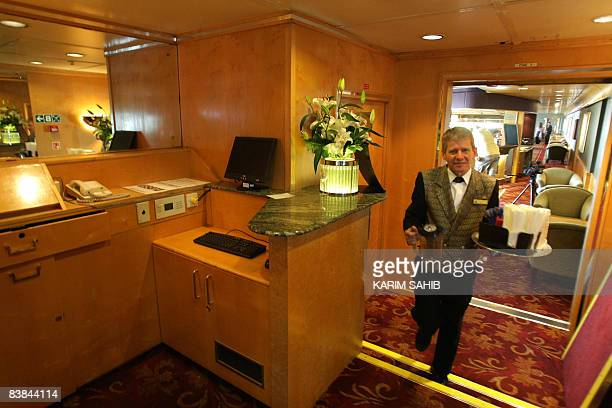 An employee carries a tray inside the Queen Elizabeth 2 cruise liner as it rests in port in Dubai on November 27 2008 The QE2 will now be completely...