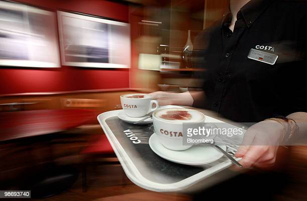 An employee carries a tray of coffees at a Costa Coffee shop in London UK on Monday April 26 2010 Whitbread Plc which own Costa Coffee announce...