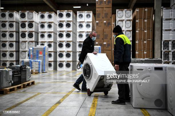An employee carries a washing-machine before inspecting it at the BSH electrical appliances company, a Back Market refurbishing company...