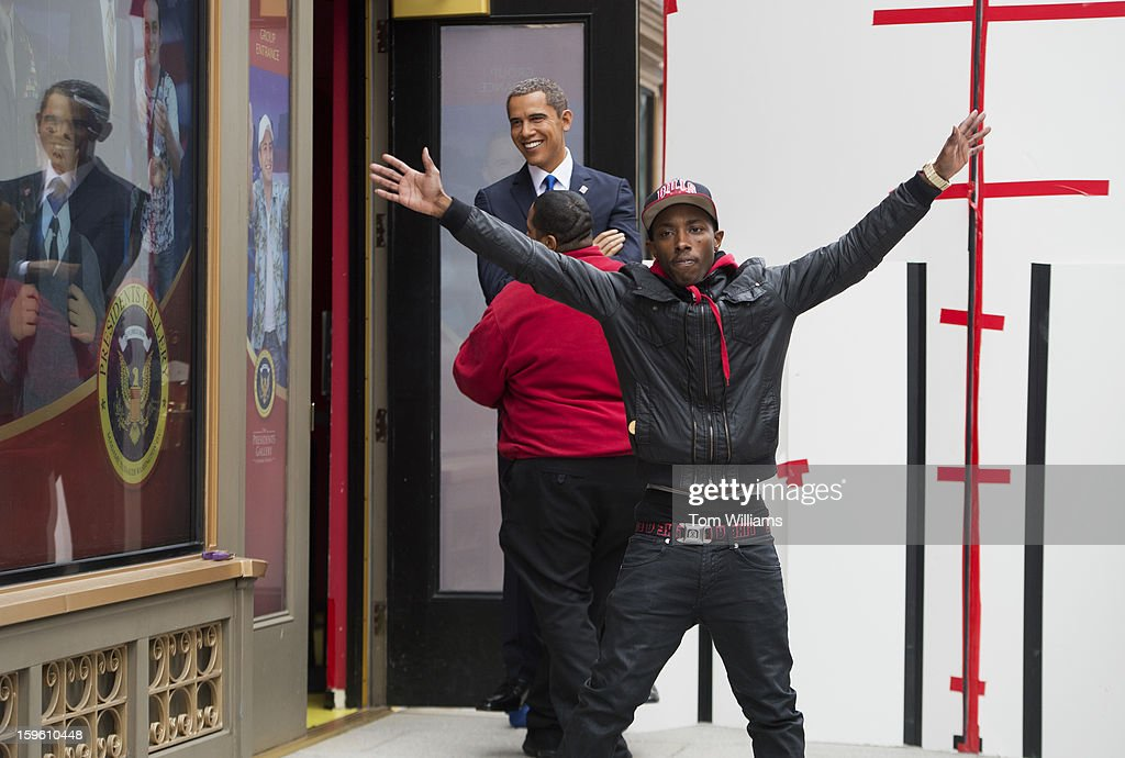 An employee carries a wax figure of President Barack Obama into Madame Tussauds wax museum after Obama and a figure of First Lady Michelle Obama arrived from an open top bus ride through downtown. The other employee seen is trying to disrupt onlookers from taking pictures.