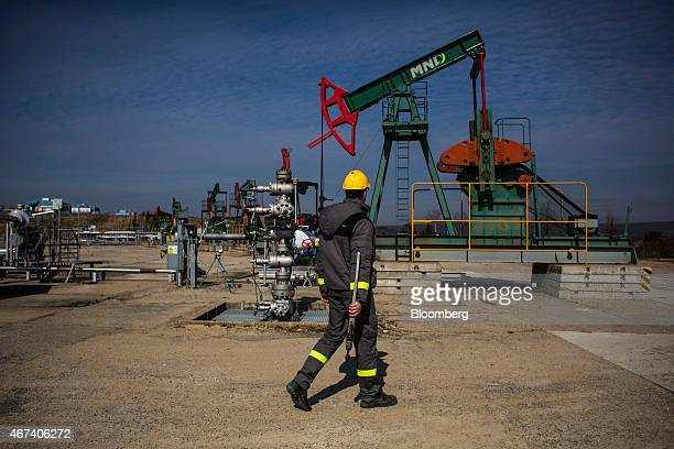 An employee carries a wrench during work on oil pumping gear also known as nodding donkeys or pump jacks at an oil plant operated by MND AS in Uhrice...