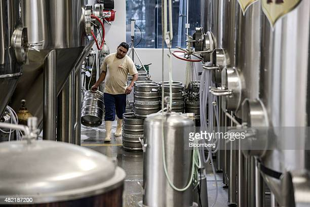 An employee carries an empty keg to be filled with beer at the Wunder Bier brewery in Blumenau Brazil on Thursday July 16 2015 Wunder Bier a craft...