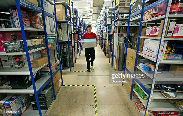 An employee carries an item through the warehouse at an Argos store operated by Home Retail Group Plc in Enfield UK on Wednesday Sept 7 2011 Home...