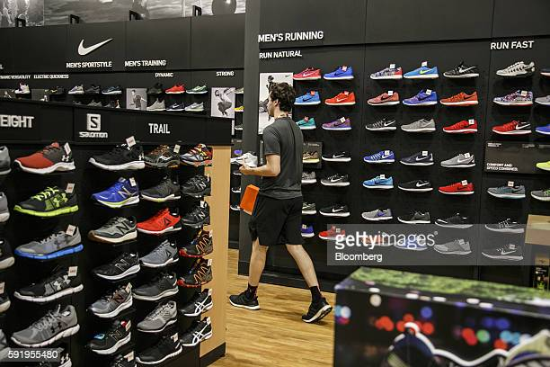 An employee carries Nike Inc sneakers for a customer at a Dick's Sporting Goods Inc store in Sterling Heights Michigan US on Thursday Aug 18 2016...