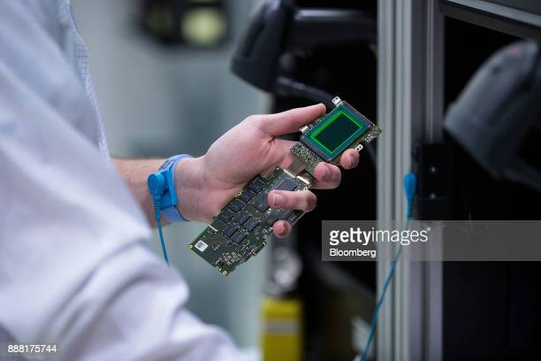 An employee carries out checks on a 24megapixel sensor ahead of calibration during assembly of Leica M10 rangefinder digital camera at the Leica...