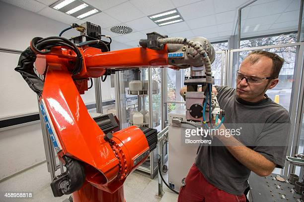 An employee carries out maintenance work on a robotic arm manufactured by Reis Group Holding GmbH in a test laboratory at Holcim Ltd's cement plant...