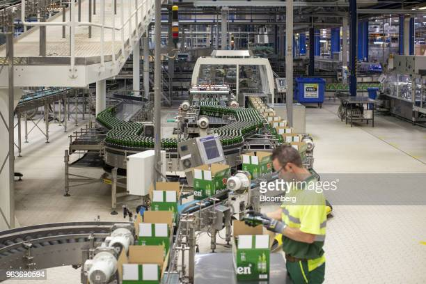 An employee carries out quality checks as Heineken beer bottles move along a packaging conveyor at the Heineken NV brewery in Zoeterwoude Netherlands...