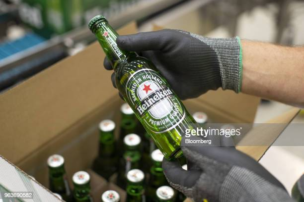 An employee carries out quality checks on a Heineken beer bottle on a packaging conveyor at the Heineken NV brewery in Zoeterwoude Netherlands on...