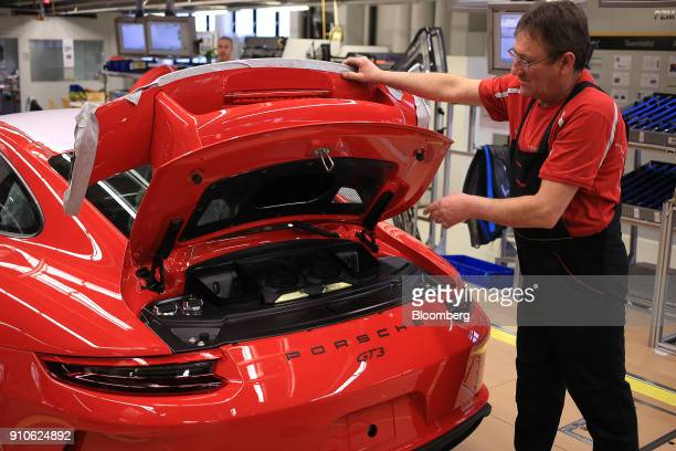 An employee carries out quality checks on the rear spoiler and ventilation of a Porsche GT 3 luxury automobile on the production line inside the...