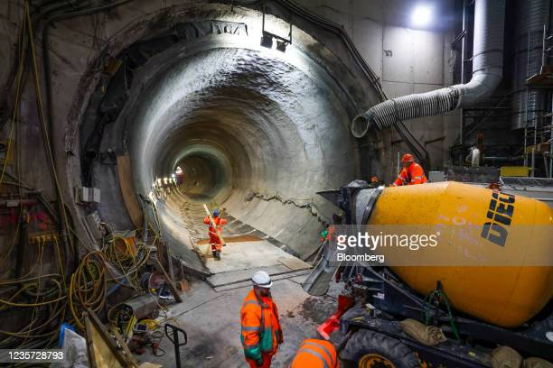 An employee carries planks of wood through the main tunnel at the Thames Tideway Tunnel super sewer construction project in London, U.K., on...