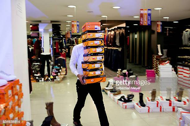 An employee carries shoeboxes through the new Maximall in the wealthy Mansour district of Baghdad 10 years after the US led invasion Iraq continues...